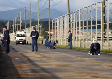 車4台が衝突、4人が死亡した事故現場でブレーキ痕などの痕跡を調べる捜査員ら=23日午前6時半ごろ、つがる市森田町