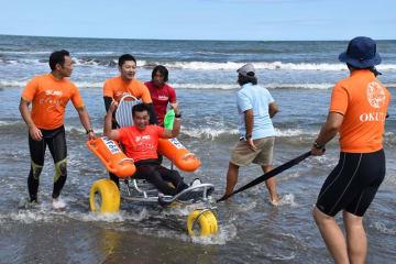 競技を終え、海岸用車いすで海から上がる選手=23日、いすみ市