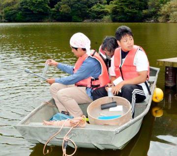 ボートに乗って亀ケ池の水質を調べる愛媛大生ら