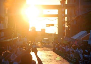 鳥居の間に沈む夕日を眺める参詣者ら=23日、大阪市天王寺区の四天王寺