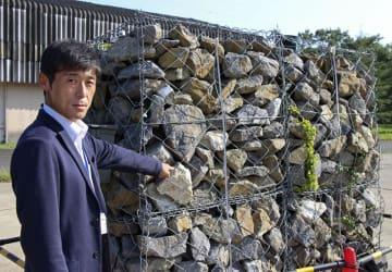 金網で覆った「蛇籠」構造の石積みの壁について説明する防災科学技術研究所の中澤博志主幹研究員=5日、茨城県つくば市