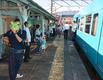 【カエルの面を着けて列車の乗客を迎える松下太紀さん(左)=23日、和歌山県印南町印南で】