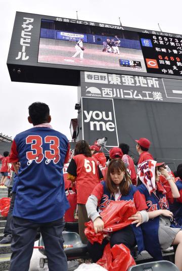 試合終了後も帰らずに、電光掲示板で2位のヤクルト戦を見つめる広島ファン。マジックナンバーは1のままで、優勝決定は持ち越しとなった=マツダ