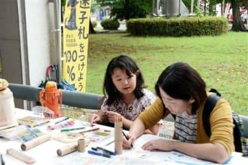 犬猫の首輪につける「迷子札」作りをする親子連れ=熊本市東区
