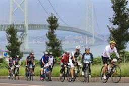 コース終盤の上り坂。明石海峡大橋を背に、力を振り絞ってペダルをこぐ参加者=24日午後、淡路市岩屋(撮影・辰巳直之)