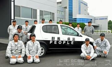 「群馬県警」に似せて「群馬県民」と塗装された車を囲む太田自動車大学校車体整備学科の14人