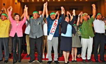 ガンバロー三唱で気勢を上げる仲西春雅氏(左から4人目)ら=24日、宜野湾市民会館