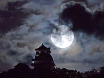 厚い雲の切れ間に輝く中秋の名月。岐阜城と幻想的な二重奏を奏でた=24日午後6時48分、岐阜市内