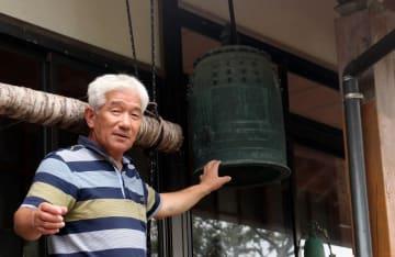 マリア観音像が見つかった興禅寺で梵鐘を調べる和泉さん=佐世保市黒島町
