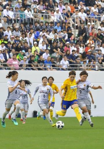 青森県で初めて行われたなでしこリーグの試合。女子選手の力強いプレーを、集まった多くの観客が熱心に見つめていた=24日、八戸市のダイハツスタジアム