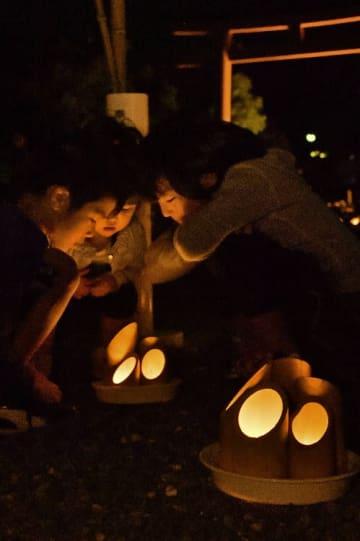 境内に並んだ竹灯籠の柔らかな明かりを楽しむ子どもたち=24日午後6時45分ごろ、八戸市小中野8丁目の御前神社