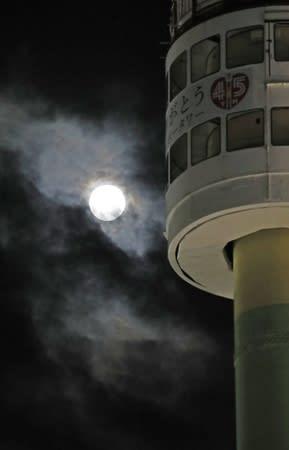 雲の切れ間から一瞬顔を出した中秋の名月とレインボータワー=24日午後8時ごろ、新潟市中央区