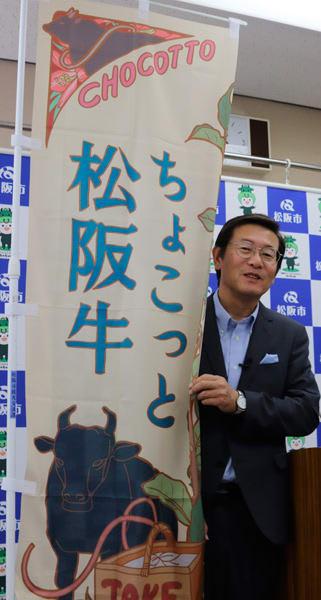 【「ちょこっと松阪牛」参加店舗ののぼりを示す竹上市長=松阪市役所で】