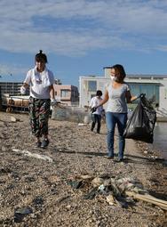 漂着ごみが散乱する海岸を清掃する人たち=19日午後、西宮市西波止町