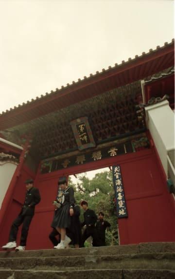 ※屋根をふき替え、扉や額を塗装した崇福寺の第一峰門。全体に濃い虹色が映える=長崎市鍛冶屋町