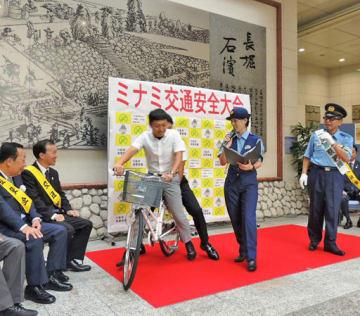 円広志さん(右)のトークショーに2人乗りで乗り込む署員。寸劇で危ない運転を訴えた=24日、大阪市中央区のクリスタ長堀