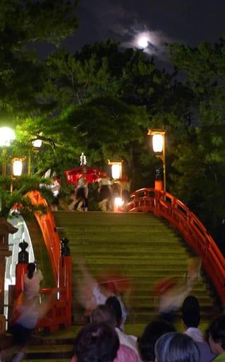 月明かりの下、反橋周辺で披露された住吉踊=24日夜、大阪市住吉区の住吉大社
