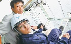 ガントリークレーンの操作に挑戦する高校生(右)。ガラス張りの眼下に海が広がる