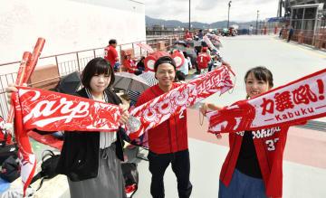 優勝マジック「1」としているプロ野球広島の試合観戦のため、午前中から球場前に並び撮影に応じるファン=25日、広島市
