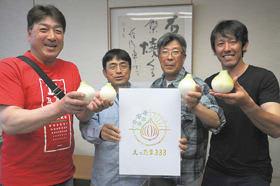 「えったま333」のロゴマークと堀篭さん(左から2人目)ら新タマネギを手にした生産者たち=6月