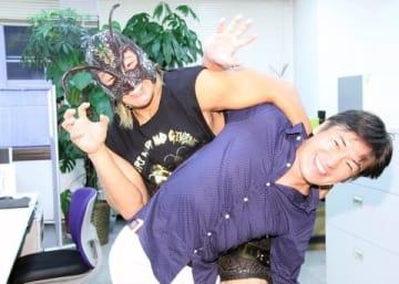編集部に来訪した映画「パパはわるものチャンピオン」のゴキブリマスク(左)