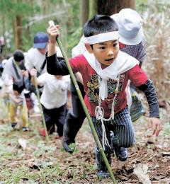 つえを突いて険しい山道を登る子どもたち