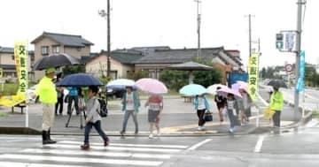警察官やボランティアに見守られながら登校する子どもたち=25日、新潟市北区