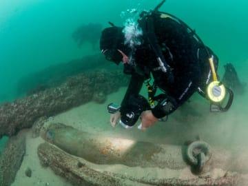 海底に沈んだ交易船の残骸を調べるダイバー=24日、リスボン郊外カスカイス沖(カスカイス市提供・ロイター=共同)