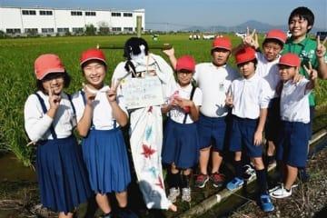 田んぼにまつわるクイズを出題しているかかしを囲む杉上小5年生=熊本市南区