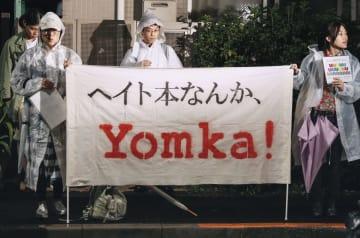 月刊誌「新潮45」を出版する新潮社の本社前でメッセージを掲げ抗議する人たち=25日夜、東京都新宿区