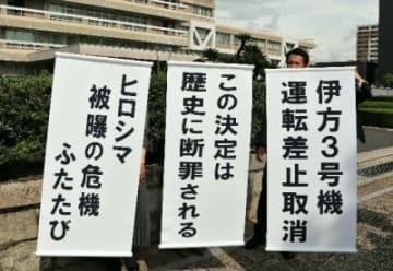 伊方原発の運転を差し止める決定が取り消され、広島高裁前で垂れ幕を掲げる住民側=25日午後1時37分、広島市中区、撮影・大久保貴浩