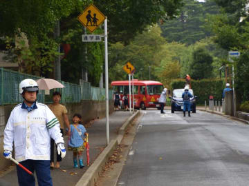 通学路で安全確認や取り締まりを行う警察官ら=25日、千葉市稲毛区