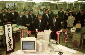 ワープロシステムの完成でテープカットする小川社長(中央左)と菊池技師長=長崎新聞社
