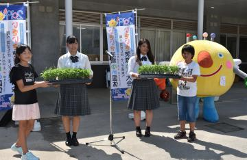 花いっぱい運動の一環で小学生に花の苗を贈る高校生=7月、石岡市内