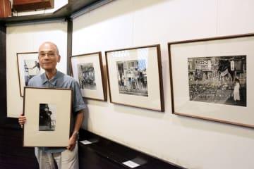 麦島勝さんが撮影した集団就職の写真を手に、追悼展をPRする前山光則さん=八代市
