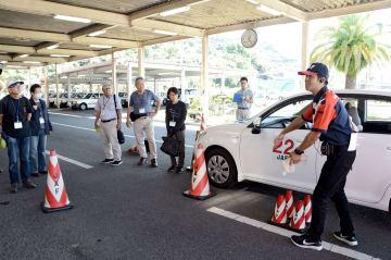 運転席の死角について、JAFの指導員(右)から説明を受ける参加者=八代市