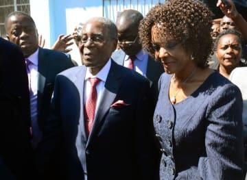 ジンバブエ大統領選の投票を終え、群衆に囲まれるムガベ氏(中央)と妻グレース氏=7月30日、首都ハラレ(共同)
