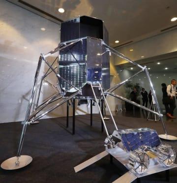 宇宙ベンチャー「ispace」が報道陣に公開した、月着陸船と月面探査車(右下)の実物大模型=26日午後、東京都港区