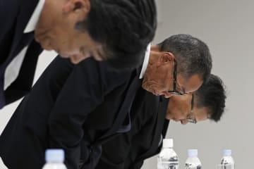 記者会見で、燃費測定などの不正について謝罪する日産自動車の山内康裕執行役員(中央)ら=26日午後、横浜市の本社