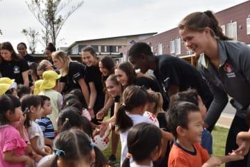 握手して交流を深めるオガール保育園の園児と、カナダのバレーボール女子代表選手