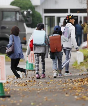 上着を羽織って避難所から登校する小学生ら=27日午前、北海道厚真町