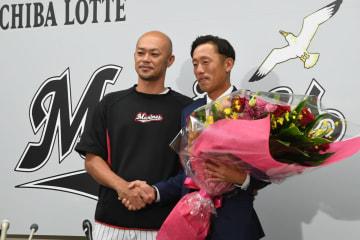 引退会見でロッテ福浦から花束を受け取る岡田(右)=千葉市のZOZOマリンスタジアム