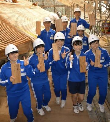 天台寺の屋根の工事に使われる板に、夢や希望を書いた二戸市立御返地中の生徒=20日、同市浄法寺町