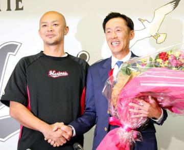 引退会見で福浦(左)から花束を受け取り笑顔をみせる千葉ロッテ・岡田=26日、千葉市美浜区のZOZOマリンスタジアム