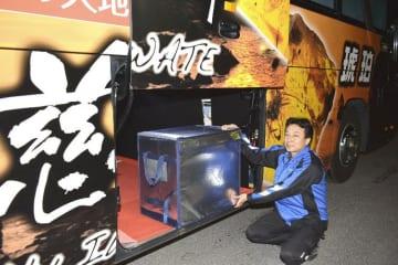 高速夜行バス「岩手きずな号」に保冷ケースを積み込む関係者=26日夜、久慈市