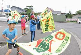 元気良く交通安全旗を振る壮瞥小2年生たち