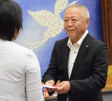 本県の子どもたちの成長を願い目録を手渡す岡田啓会長(右)