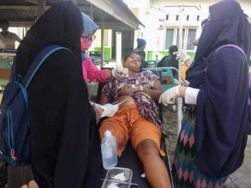 インドネシア・スラウェシ島中部中スラウェシ州で起きた地震で、治療を受ける住民=28日(国家災害対策庁提供・共同)