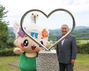 中井中央公園に設置されたハート型のモニュメントと杉山町長、中井町の公式キャラクター「なかまる」=同町提供