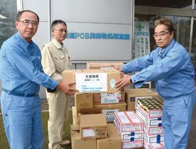 石川さん(右)に支援物資を手渡す大島副所長(左)。中央は吉永社長